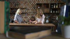 Vrolijke familie die koekjes in de keuken voorbereiden stock footage