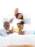Vrolijke familie die ontbijt in de slaapkamer heeft Royalty-vrije Stock Foto's