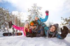 Vrolijke familie die op sneeuw genieten van Stock Foto's