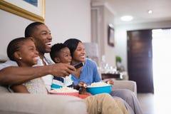 Vrolijke familie die popcorn hebben terwijl het letten van op televisie stock fotografie