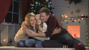 Vrolijke familie die pret hebben die weinig dochter, de vrije tijd van de Kerstmisvooravond kietelen stock footage