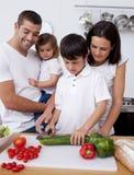Vrolijke familie kokende groenten samen stock foto's