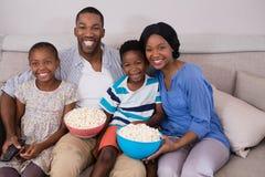 Vrolijke familie met popcornkommen die op bank situeren stock afbeelding
