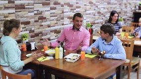 Vrolijke familie met tieners die lunch in comfortabele koffie hebben stock footage