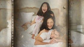 Vrolijke familie van vier die over elkaar in bed liggen stock videobeelden