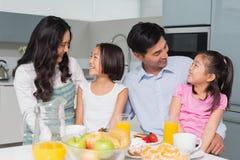 Vrolijke familie van vier die van gezond ontbijt in keuken genieten Royalty-vrije Stock Afbeeldingen