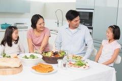 Vrolijke familie van vier die van gezonde maaltijd in keuken genieten Stock Foto
