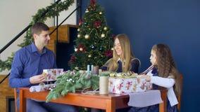 Vrolijke famiy verpakkende Kerstmisgiften thuis stock footage