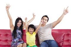 Vrolijke geïsoleerde familiezitting op bank Stock Fotografie