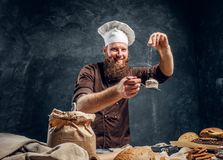 Vrolijke gebaarde bakker die wat bloem op zijn vers gemaakte muffin naast een lijst bestrooien royalty-vrije stock foto