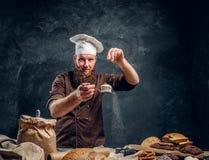 Vrolijke gebaarde bakker die wat bloem op zijn vers gemaakte muffin naast een lijst bestrooien royalty-vrije stock fotografie