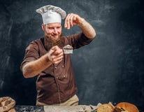 Vrolijke gebaarde bakker die wat bloem op zijn vers gemaakte muffin naast een lijst bestrooien stock foto