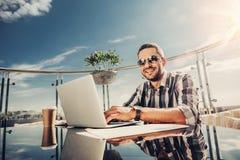Vrolijke gebaarde mens in zonnebril bij openluchtkoffie met laptop royalty-vrije stock afbeelding