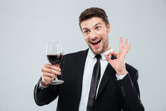 Vrolijke gedronken zakenman die rode wijn drinken en o.k. teken tonen royalty-vrije stock foto