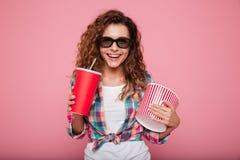 Vrolijke gelukkige dame met kola en popcorn die 3d glazen dragen Stock Afbeeldingen
