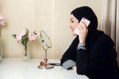 Vrolijke gelukkige vrij moslimvrouw die en mobiele celtelefoon zitten met behulp van die vriend het babbelen verzoeken tijdens va stock fotografie
