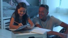 Vrolijke gevende vader die haar dochter met haar huiswerk helpen stock footage