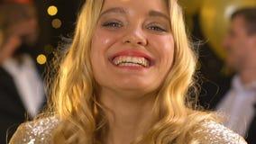 Vrolijke glimlachende dame die op confettien blazen en luchtkus maken bij verjaardagspartij stock videobeelden