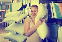 Vrolijke glimlachende vrouw die donsachtig hoofdkussen houden stock afbeelding