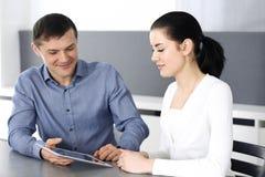Vrolijke glimlachende zakenman en vrouw die met tabletcomputer werken in modern bureau Headshot op vergadering of het werk stock afbeelding