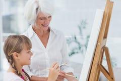 Vrolijke grootmoeder en kleindochter die samen schilderen stock fotografie