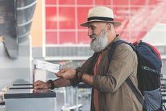 Vrolijke grootvader het standhouden kaart bij luchthaven Royalty-vrije Stock Afbeelding