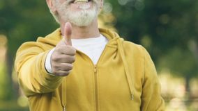 Vrolijke grootvader in sportief kostuum die, gezonde levensstijl duim-omhoog tonen stock videobeelden