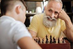 Vrolijke hogere mens die bij kleinzoon glimlachen terwijl het spelen van schaak royalty-vrije stock afbeelding