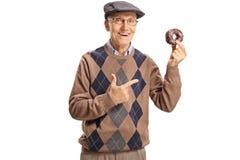 Vrolijke hogere mens die een chocoladedoughnut houden en op het richten royalty-vrije stock afbeelding