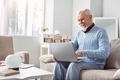 Vrolijke hogere mens die zijn laptop in woonkamer met behulp van royalty-vrije stock afbeelding