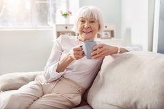 Vrolijke hogere vrouw het drinken koffie op bank stock foto's
