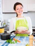 Vrolijke huisvrouwen kokende rijst in pan Stock Afbeelding