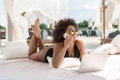 Vrolijke jeugdige mulatvrouw die door gadget op vakantie communiceren royalty-vrije stock fotografie