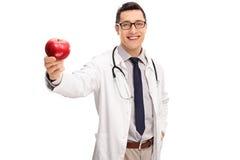 Vrolijke jonge arts die een appel houden Royalty-vrije Stock Afbeelding