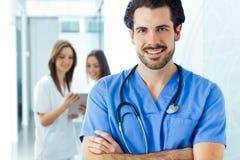 Vrolijke jonge arts die zijn team leidt Stock Afbeeldingen