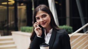Vrolijke jonge bedrijfsvrouw die zich dichtbij bureaucentrum bevinden, die op smartphone spreken Zij die de camera onderzoeken stock videobeelden