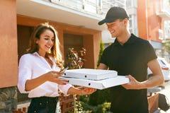 Vrolijke jonge bezorger die een pizzadoos houden terwijl geïsoleerd op wit Koerier Giving Woman Boxes met Voedsel in openlucht royalty-vrije stock foto