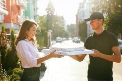 Vrolijke jonge bezorger die een pizzadoos houden terwijl geïsoleerd op wit Koerier Giving Woman Boxes met Voedsel in openlucht royalty-vrije stock afbeelding