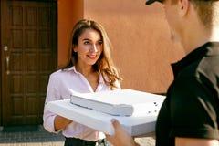 Vrolijke jonge bezorger die een pizzadoos houden terwijl geïsoleerd op wit Koerier Giving Woman Boxes met Voedsel in openlucht stock foto