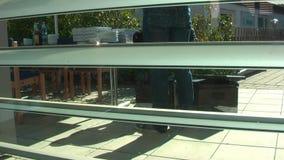 Vrolijke jonge bezorger die een pizzadoos houden terwijl geïsoleerd op wit Koper en verkoper stock footage