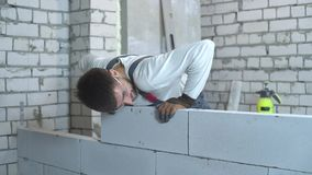 Vrolijke jonge bouwer die in het werkslijtage blokken leggen bij bouwwerf stock videobeelden