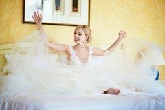 Vrolijke jonge bruid in huwelijkskleding in hotelruimte royalty-vrije stock afbeelding