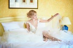 Vrolijke jonge bruid in huwelijkskleding in hotelruimte stock foto