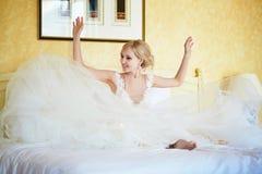 Vrolijke jonge bruid in huwelijkskleding in hotelruimte royalty-vrije stock fotografie