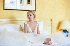 Vrolijke jonge bruid in huwelijkskleding in hotelruimte royalty-vrije stock foto