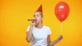 Vrolijke jonge dame in de blazende hoorn van de partijhoed, die rode ballon, verjaardag houden stock videobeelden