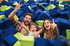 Vrolijke jonge familie met hun kleine zoon het besteden tijd stock foto's