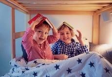 Vrolijke jonge geitjes, broers die pret hebben, die met boeken op het stapelbed tijdens bedtijd spelen stock foto