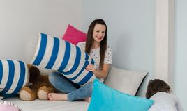 Vrolijke jonge geitjes en ouders die hoofdkussenstrijd op bed hebben thuis stock afbeelding