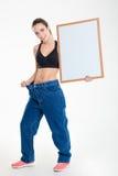 Vrolijke jonge geschiktheidsvrouw die in grote jeans lege raad houden Stock Fotografie